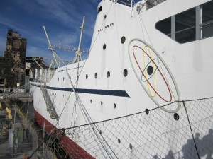 The NS Savannah is docked at a pier location which is largely blocked from view by land by a giant grain elevator.  This view shows the port side of the ship from the gangway leading to the passenger reception area.  Photo for ANS by Paul Bowersox.