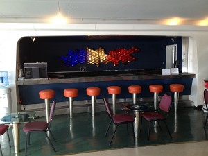 This is the Veranda, the public (passenger) bar / lounge on the NS Savannah.  The lighted, sculptured wine rack behind the bar is meant to be a representation of the periodic table and is one of many striking decorative features in this space.  A glass bulkhead looks aft from this space over the former swimming pool and shuffleboard areas. Photo for ANS by Will Davis.