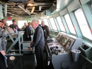 The tour visits the bridge of the Savannah.  The ship's control console is at right, under the bridge windows, with the right most device on the upper section being the engine order telegraph, and the device to the left of it being the shaft RPM indicator.  The ship's wheel is just out of view on the left of the photo.  Photo for ANS by Paul Bowersox.